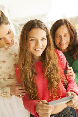 three generation: Three generation women with mobile phone smiling Stock Photo
