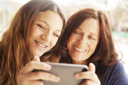 only women: Happy girl and grandmother with cellphone Stock Photo