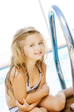 little blonde girl: Little girl having fun in swimming pool Stock Photo
