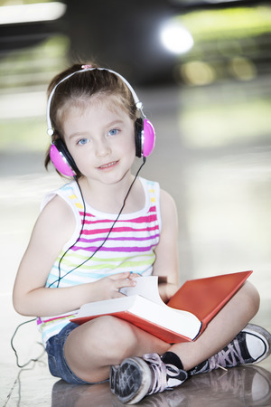 gir: Little girl with book and headphones Stock Photo