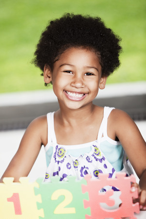 curly hair child: African american girl playing with numbers