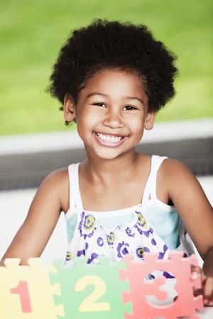 cabello rizado: Chica afroamericana jugando con los números