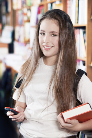 celphone: Girl in library with book and mobile phone Stock Photo