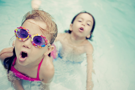 young boy in pool: Little friends having fun in swimming pool