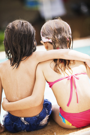 young boy in pool: Little boy and girl in swimming pool