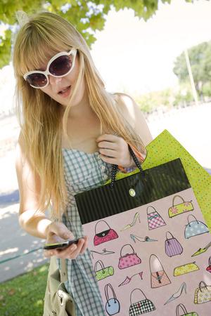adn: Mujer con bolsas de la compra adn tel�fono m�vil Foto de archivo