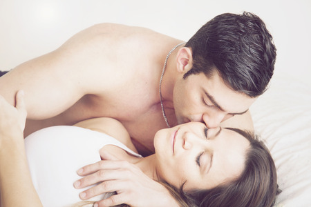 sexy couple in bed: Young couple kissing in bed Stock Photo