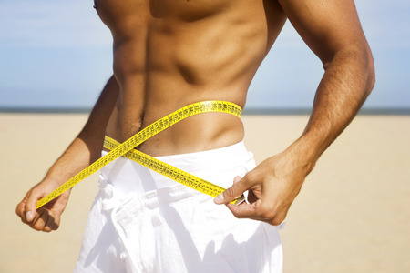 athletic body: Sexy man body with centimeter on the beach Stock Photo