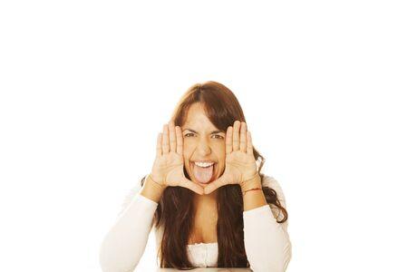 sticking out tongue: Mujer que se pega hacia fuera la lengua