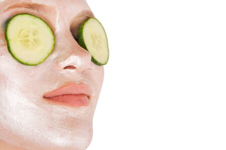 facial: Woman with facial mask and cucumbers Stock Photo