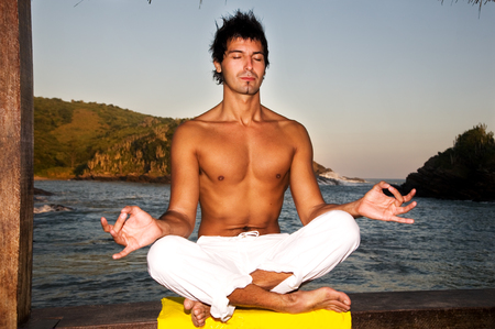 sexual position: Young man meditating on the beach