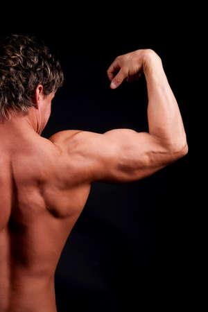 biceps: Bodybuilder showing biceps and back
