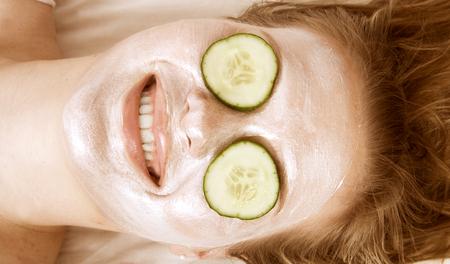 masaje facial: Mujer con la máscara facial y pepinos