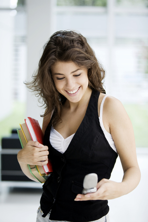 cel: Happy teen student smiling with books sending text message