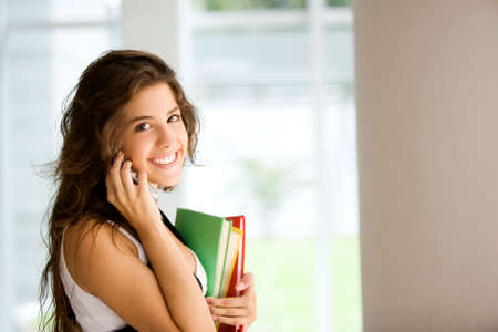 cel: Happy teen student smiling with books on the phone