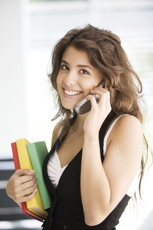 cel: Happy teen student on the phone