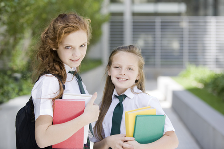 cel: Happy school girls smiling with books Stock Photo