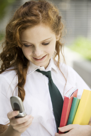 cel: Happy school girl smiling with  mobile phone and books Stock Photo