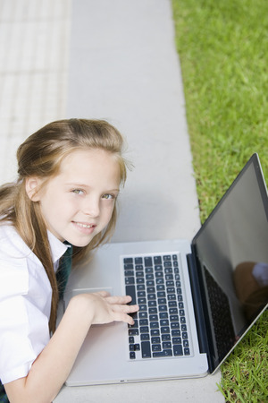 cel: Happy school girl smiling with computer Stock Photo