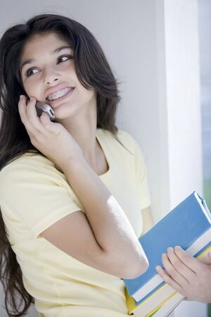 cel: Teen student smiling with books on the phone Stock Photo