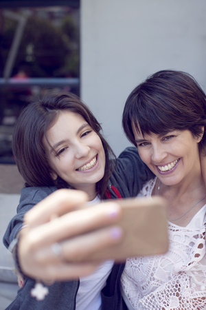 latin mother: Mother and daughter taking a selfie