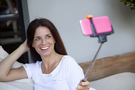 self   portrait: Happy woman taking a self portrait with mobile phone Stock Photo