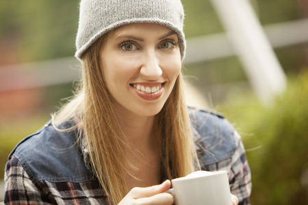 blond girl: Happy young woman drinking coffee