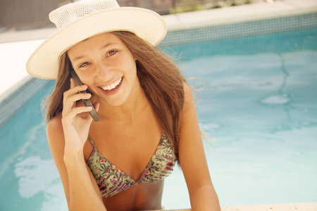 teen bikini: Happy teen girl in swimming pool on the phone Stock Photo