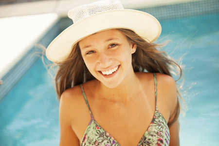 teen bikini: Happy teen girl in swimming pool with hat
