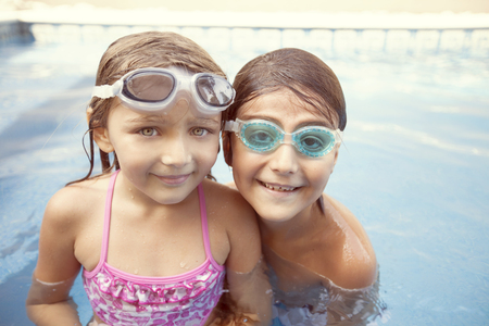 cute girl: Happy boy and girl in swimming pool with goggles Stock Photo
