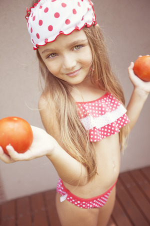 swimsuits: Happy girl with tomatoes Stock Photo