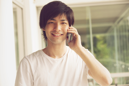 japanese people: Japanese man smiling on the phone Stock Photo