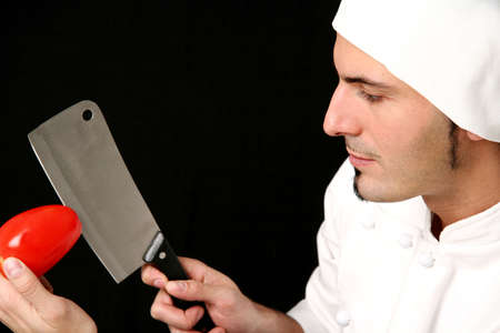 young knife: Young cook with knife and tomato