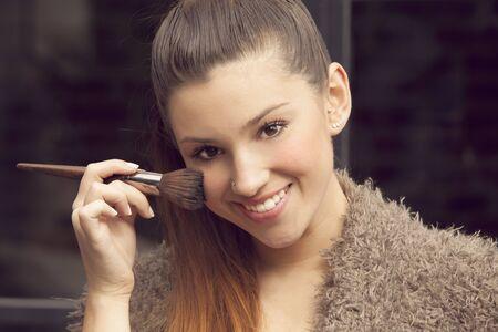 mujer maquillandose: Mujer joven que aplica maquillaje Foto de archivo