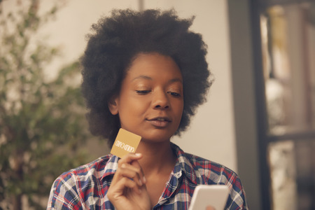 cel: African american woman with mobile phone and credit card Stock Photo