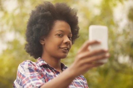 cel: African american woman taking selfie with mobile phone