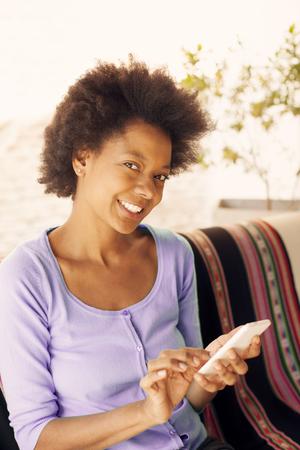 sending: Afro woman sending text message
