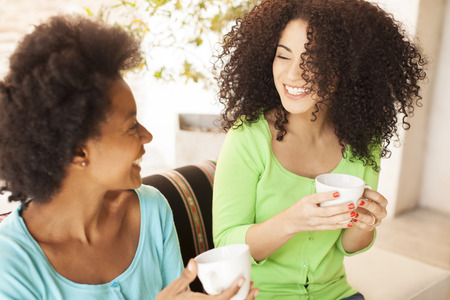 Afro amigos que hablan con café Foto de archivo