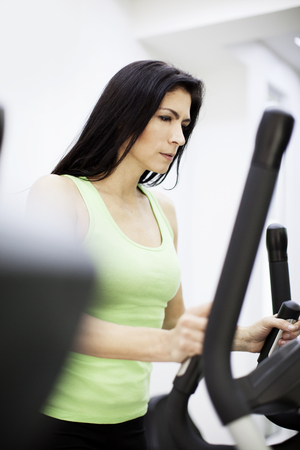 elliptical: Woman in fitness center, exercising in elliptical machine Stock Photo