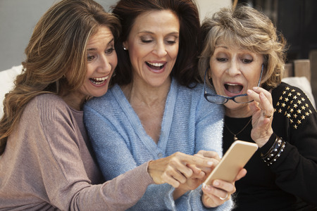 cel: Happy group of women having fun with mobile phone outdoors Stock Photo