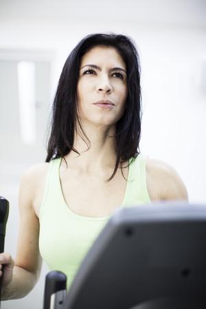 eliptica: Mujer en el gimnasio, el ejercicio en una m�quina el�ptica