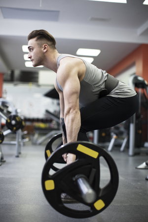 Young muscular man exercising with barbell in fitness center