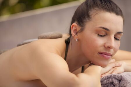 lastone: Happy latin young woman enjoying relaxing lastone therapy massage in spa Stock Photo