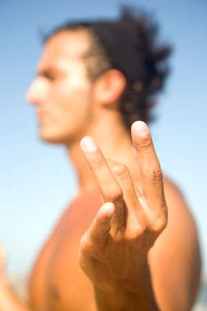 man meditating: Young man meditating doing yoga on the beach