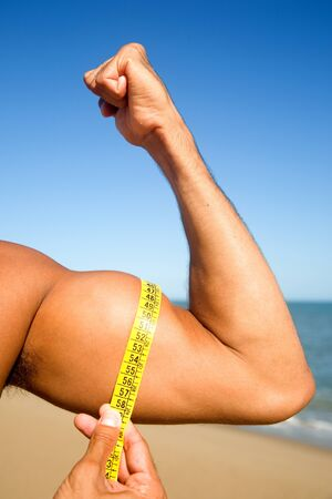 flexing: Man flexing biceps with centimeter on the beach Stock Photo