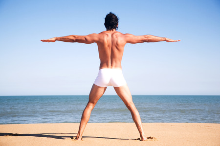 Young shirtless man exercising on the beach