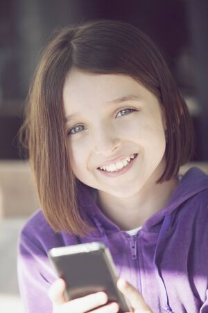 cel: Happy little girl with mobile phone Stock Photo