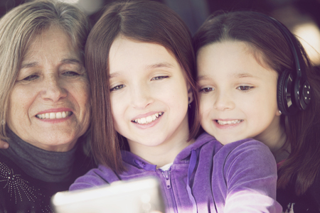 cel: Happy little girls with grandmother having fun with mobile phone