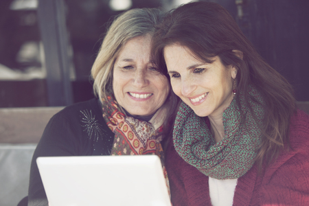 daugther: Happy senior mother and daugther with digital tablet