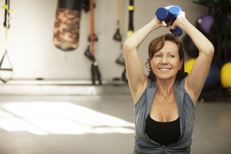 senior woman exercising: Happy senior woman exercising with dumbbell at fitness center Stock Photo